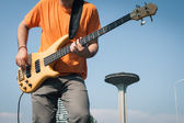 Detail of a young musician playing bass guitar — Stock Photo