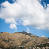 Big cloud on a high grassy hill — Stock Photo