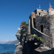 Ancient castle overhanging blue sea — Stockfoto