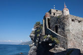 Ancient castle overhanging blue sea — Stock Photo