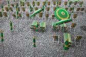 Green and yellow beach umbrellas and deckchairs on stony beach — Stock Photo