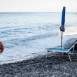 Closed beach umbrella and empty deckchair  — Stockfoto