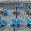 Blue deckchairs on stony beach — Stock Photo