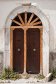 Old door shored up with wooden rods — Stock Photo