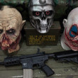 Zombie heads and rifle at Militalia 2013 in Milan, Italy — Stock Photo