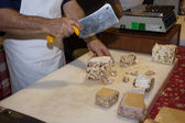 Man cutting a piece of torrone sweet at Golosaria 2013 in Milan, Italy — Stock Photo