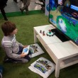 Постер, плакат: Child playing video games at G come giocare in Milan Italy