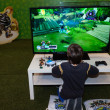 Stock Photo: Child playing video games at G! come giocare in Milan, Italy
