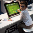 Stock Photo: Child playing video game at G! come giocare in Milan, Italy