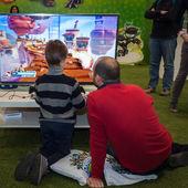 Pai e filho jogando videogame no g! venha giocare em milão, itália — Fotografia Stock