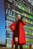 Beautiful girl with red coat talking on phone — ストック写真