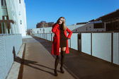 Beautiful girl with red coat talking on phone — Stok fotoğraf