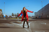 Beautiful girl posing with red coat — Stock Photo