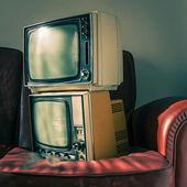 Dva vinobraní televizory na červené pohovce — Stock fotografie
