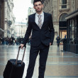 Stock Photo: Portrait of handsome young businessmwith wheeled suitcase