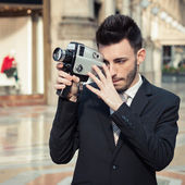 Handsome young businessman using a vintage film camera — Stock Photo