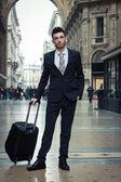 Portrait of a handsome young businessman with wheeled suitcase — Stock Photo