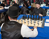 Two guys play chess at Festival del Fumetto convention in Milan, Italy — Stok fotoğraf