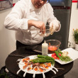 Stock Photo: Cook preparing finger food at Bit 2014, international tourism exchange in Milan, Italy