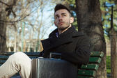 Portrait of a handsome young man sitting on a bench — Stock Photo