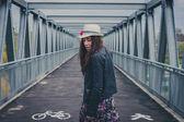 Pretty girl walking away on a bridge — Stock Photo