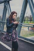 Pretty girl texting on a bridge — ストック写真