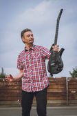 Man in short sleeve shirt holding electric guitar — Stock Photo