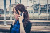 Pretty girl talking on phone along the tracks  — Stock Photo
