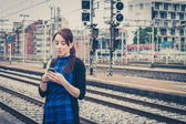 Pretty girl texting on phone along the tracks  — Stock Photo