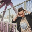 Pretty short hair girl listening to music on a bridge — Stock Photo