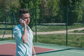 Short hair girl talking on phone in a basketball playground — Stock Photo
