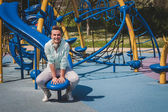 Short hair girl sitting in a children playground — Stock Photo