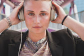 Pretty short hair girl listening to music on a bridge — Foto Stock