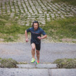 Long haired athlete running in a city park — Stock Photo #45426193