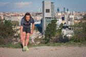 在城市公园的伸展的长发运动员 — 图库照片