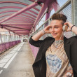 Pretty short hair girl listening to music on a bridge — Stock Photo #45443313