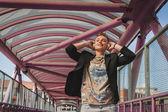Pretty short hair girl listening to music on a bridge — Stock Photo