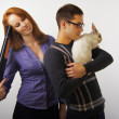Portrait of couple posing in studio with rabbit — Stock Photo