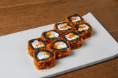 Image of black sushi with salmon on plate in restaurant — Stock Photo
