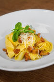 Image of pasta with chanterelle served in white dish — Stock Photo