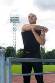 Image of muscle man stretching on stadium — Stok fotoğraf