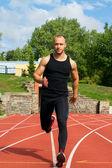Image of muscle man running on stadium — Stock Photo
