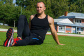 Image of muscle man sitting on stadium grass — 图库照片