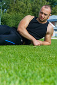 Image of muscle man sitting on stadium grass — Stock Photo