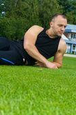 образ мышц человека, сидя на траве стадиона — Стоковое фото