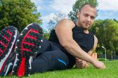 Image of muscle man sitting on stadium grass — Stock Photo