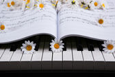 Piano keys and musical book and flower — Stock Photo