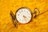 Gold pocket watch on gold cover — Stock Photo