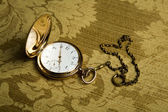 Gold pocket watch on gold cloth — Stock Photo