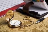 Gold pocket watch and a wall calendar and sketchpad — Stock Photo